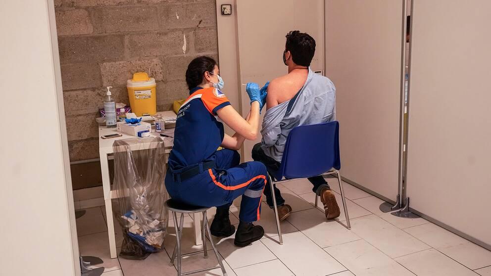 En man vaccineras på ett shoppingcentrum i Paris