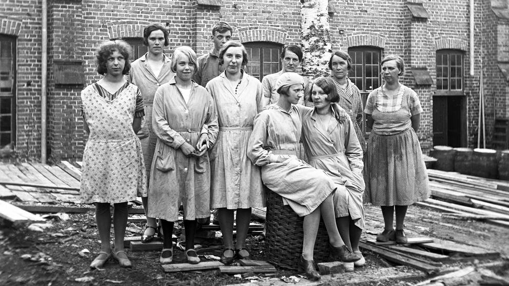 gammalt svartvitt foto av en grupp kvinnor som poserar för kameran, jord och plankor på marken, tegelbyggnad i bakgrunden