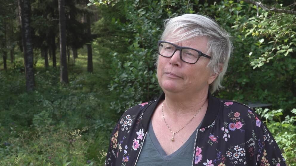En kvinna i glasögon och blommig jacka står framför en grönskande skog.