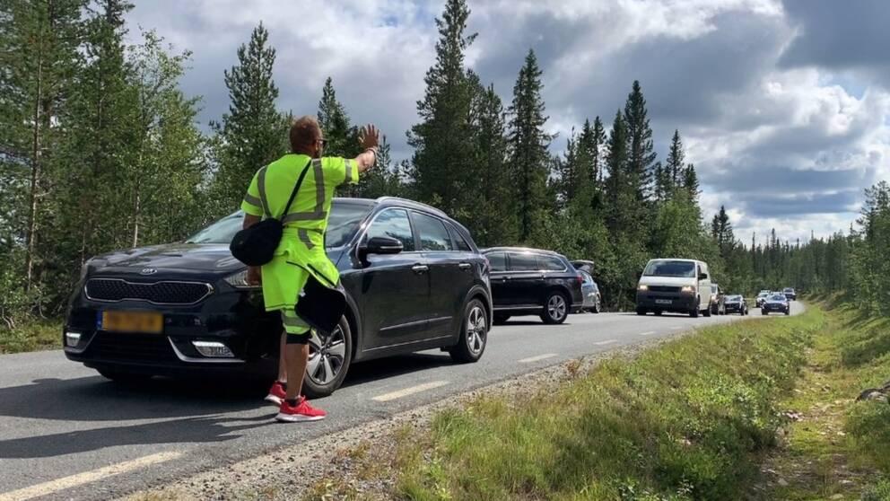 En parkeringsvakt håller upp handen och ber bilar vänta.