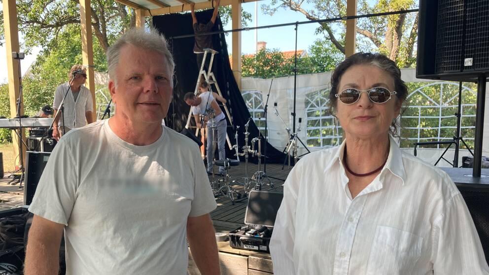 Bild på en man och en kvinna som står framför en scen. I bakgrunden syns scenarbetare som håller på att rigga upp inför en musikkonsert.