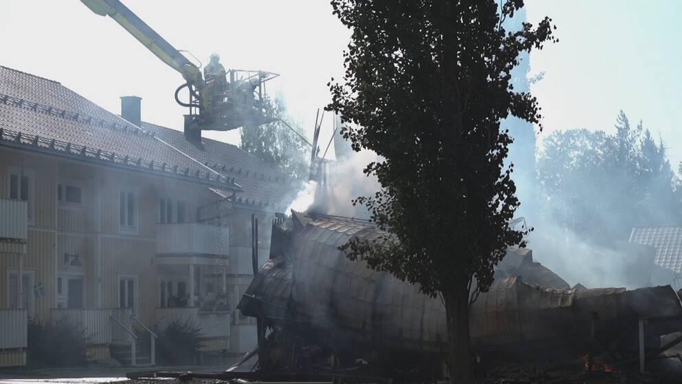 Två brandmän står i en skylift och petar med ett långt föremål på resterna av ett nedbrunner hus som ryker.