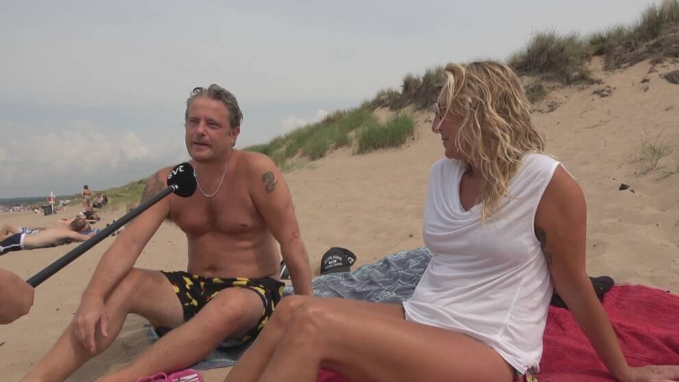 Therese Ericsson och Magnus Lindqvist sitter på varsin handduk på stranden och tittar mot svt-micken.