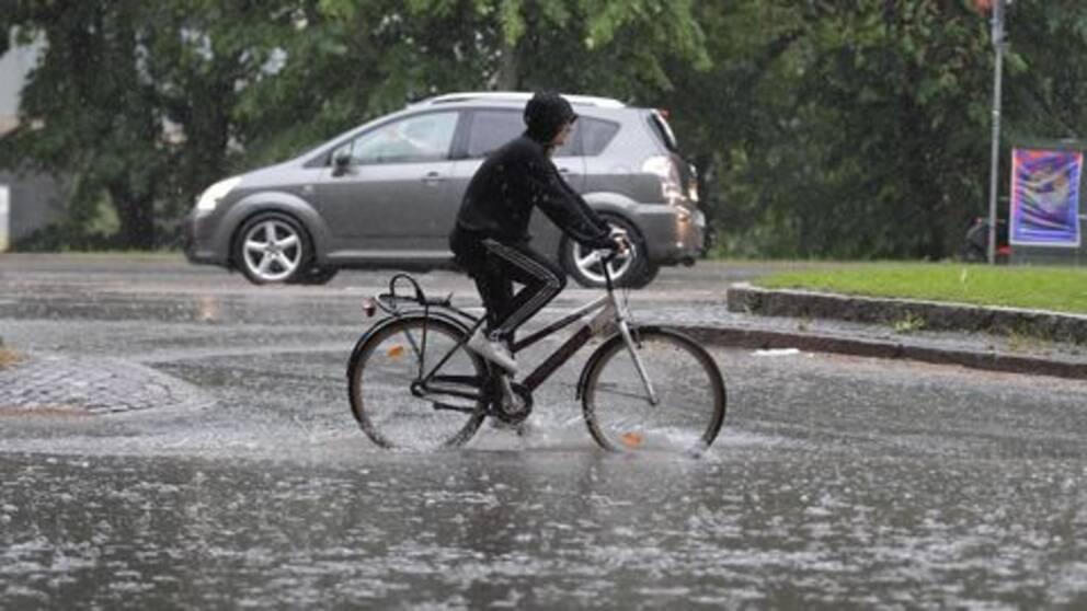 En cyklist som försöker cykla i en stor mängd vatten och regn.
