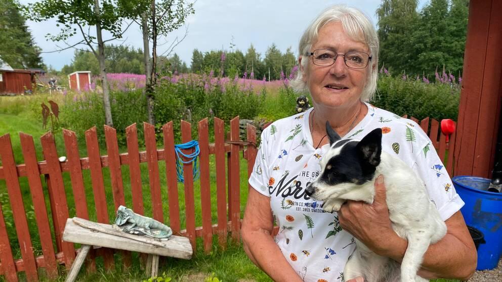 Anna Janssson håller sin hund i famnen på sin gård i Granåsjön.