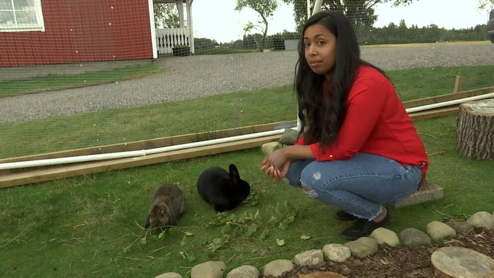 Karin Påsse sitter ner på huk vid två kaniner utomhus.
