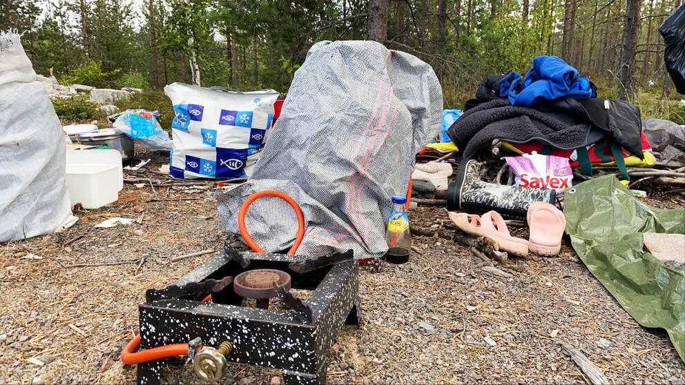 Ett tältläger med plastpåsar, en gammal gasspis och skräp.