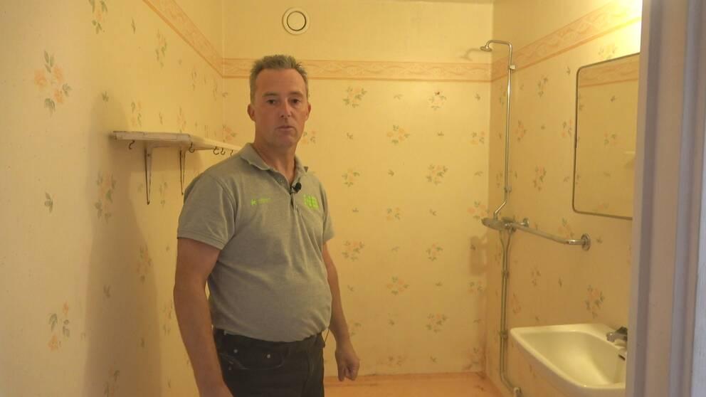 Man som står i ett av badrummen som behöver renoveras i Långshyttan