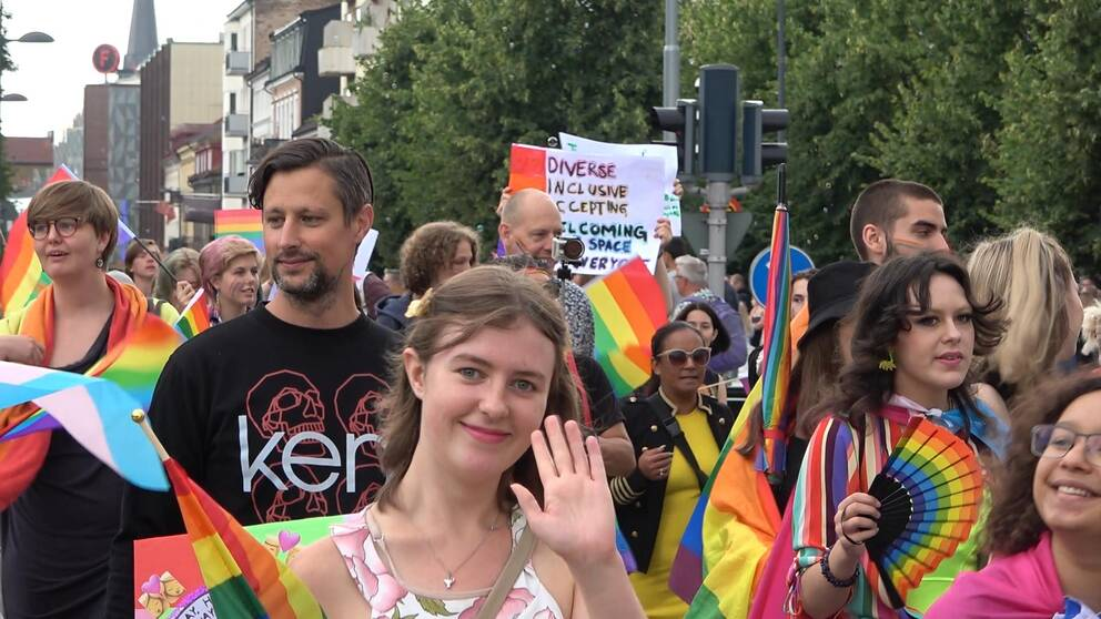 På bilden syns regnbågsflaggor och människor som går i paraden.