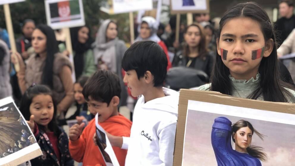 flicka med afghanska flaggan målad på kinderna, håller ett plakat med en bild, flera barn och personer med plakat i bakgrunden