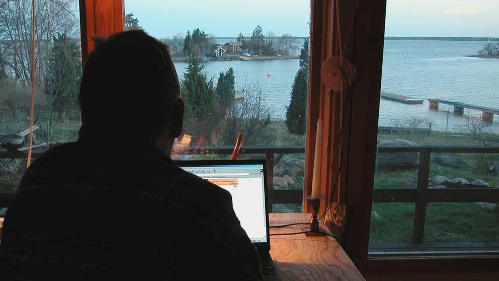 En man jobbar vid sin dator framför ett fönster.