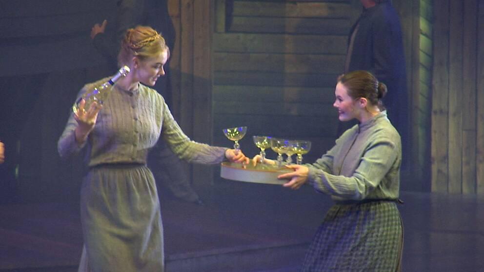 En kvinna håller en champagneflasta och en kvinna en bricka med glas