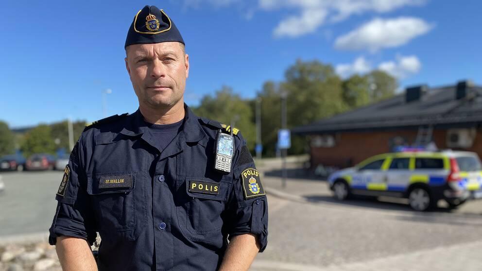 Polisen Magnus Wallin i förgrunden iklädd polisuniform. I bakgrunden en polisbil.