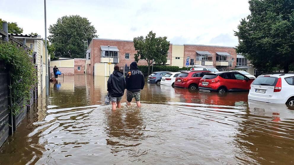 Två personer vadar i vatten i bostadsområde, Gävle. Foto: SVT