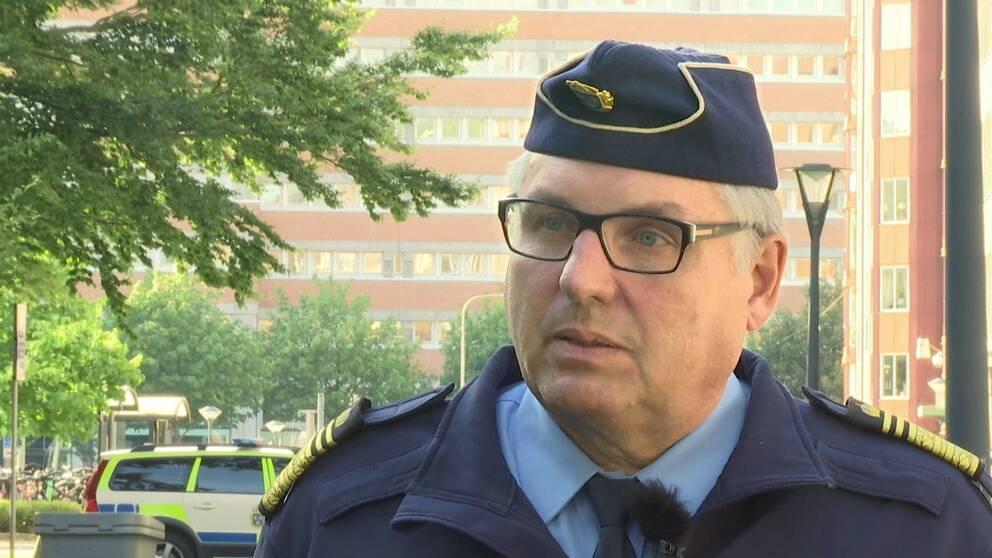 en medelålders man i polisuniform intervjuas utomhus