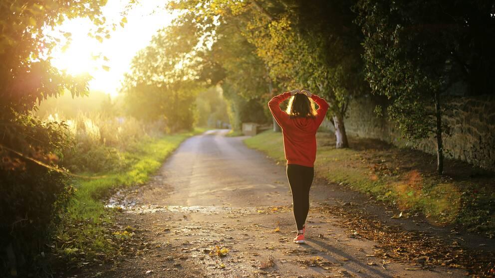 Kvinna går på gångväg i skymningsljus.
