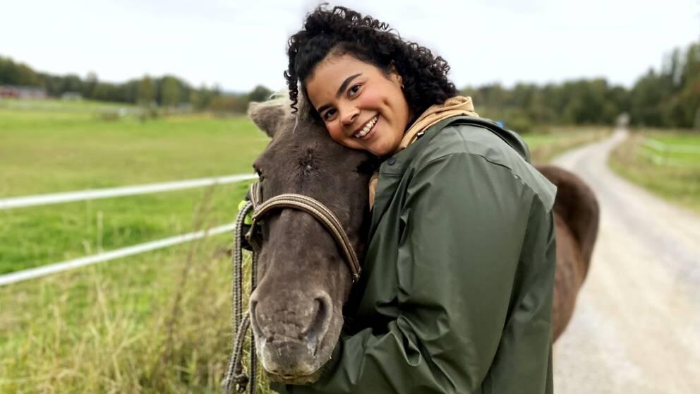 En leende Isabel Neib står till höger i bild och kramar en häst som står bredvid henne. De tittar in i kameran.