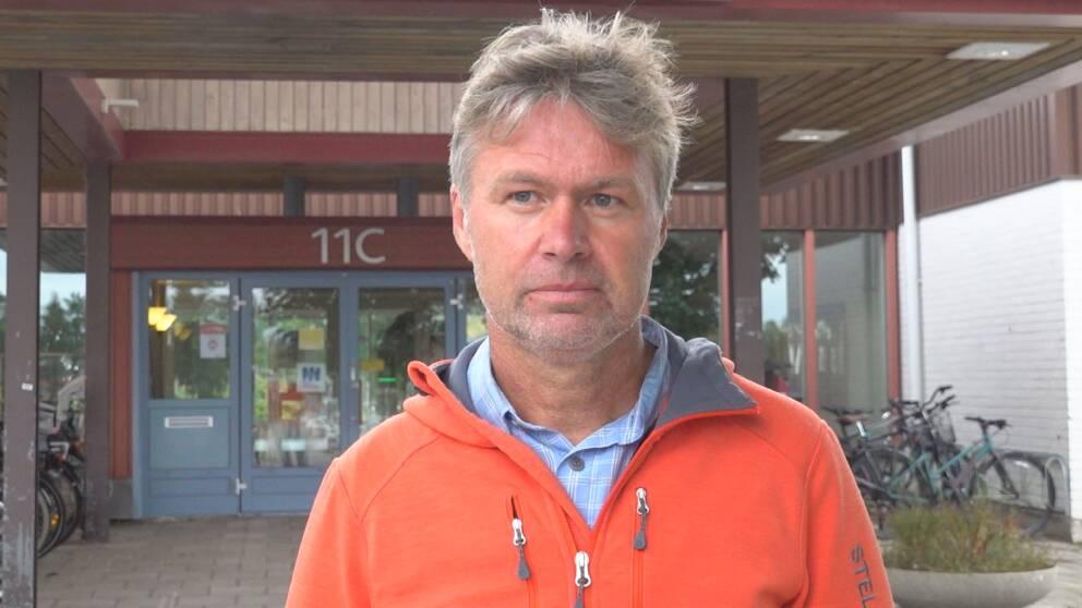 En man i orange tröja och vind i håret.