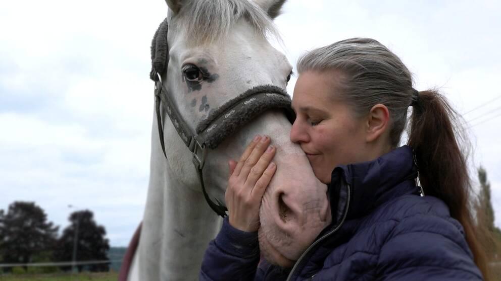 en medelålders kvinna gosar med en vit häst i hagen