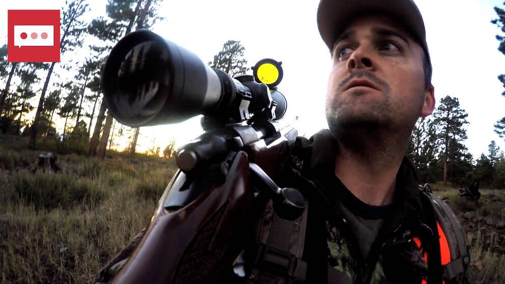 En jägare går med ett gevär över axeln