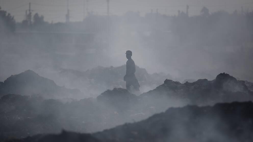 En man står på en soptipp där luften är helt höljd i rök.