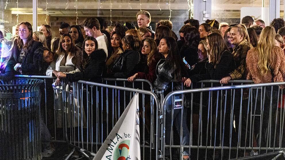 Personer står tätt packade i en kö till en nattklubb.