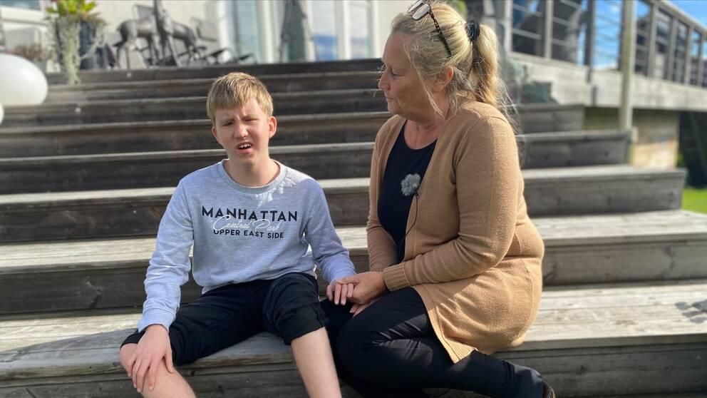 Jimmy, en ung pojke, sitter på trappan med Åsa Elmgren bredvid sig. Det är soligt väder.