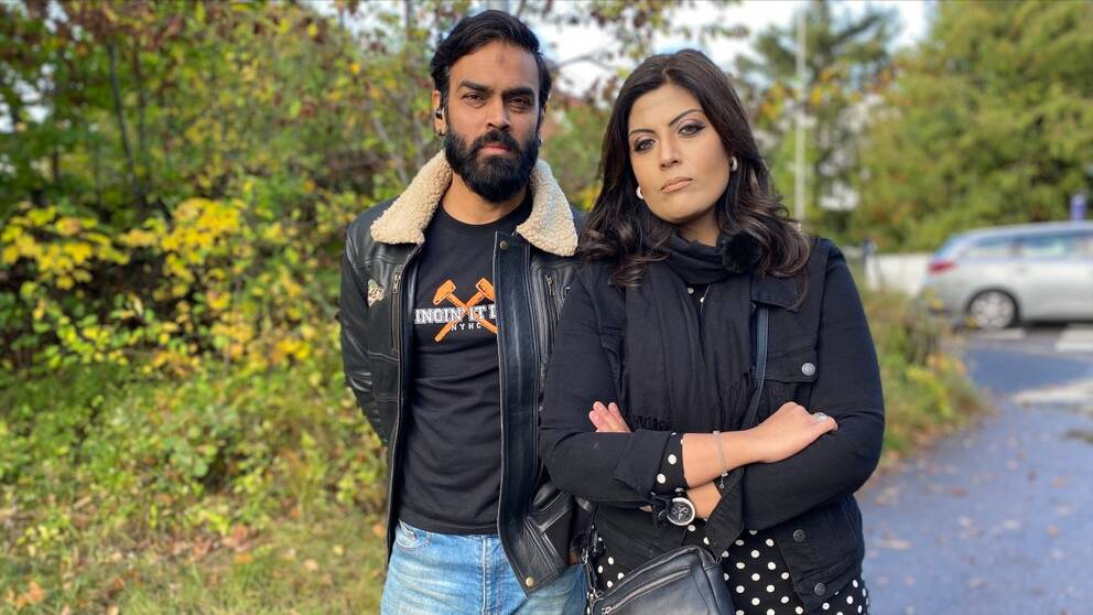 Två personer framför en buske. De ser allvarliga ut.