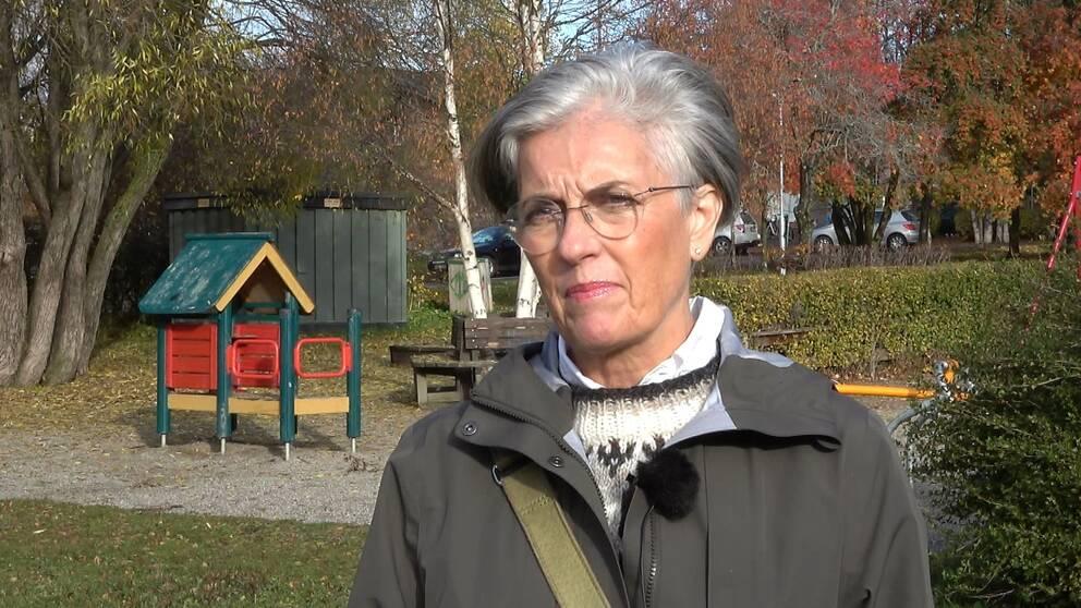 kvinna med grått hår, glasögon och grå jacka.