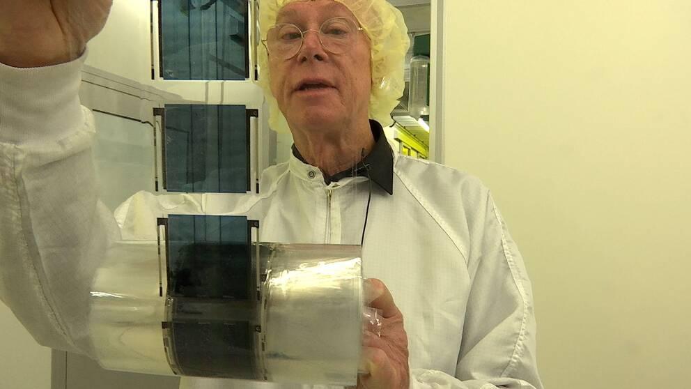Olle Inganäs tittar på rulle med ljusceller, han är professor emeritus i biomolecular and organic electronics och en av de som  grundat företaget Epishine