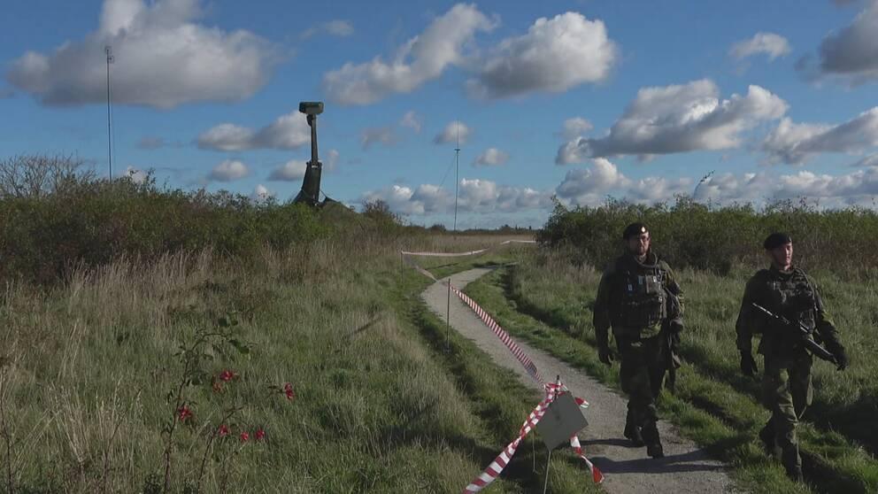 Två militärer som går beväpnade på en stig i Klagshamn natureservat med en radar i bakgrunden som bevakar luftrummet över Malmö.