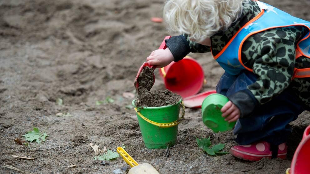 Barn gräver i sanden utanför förskola.