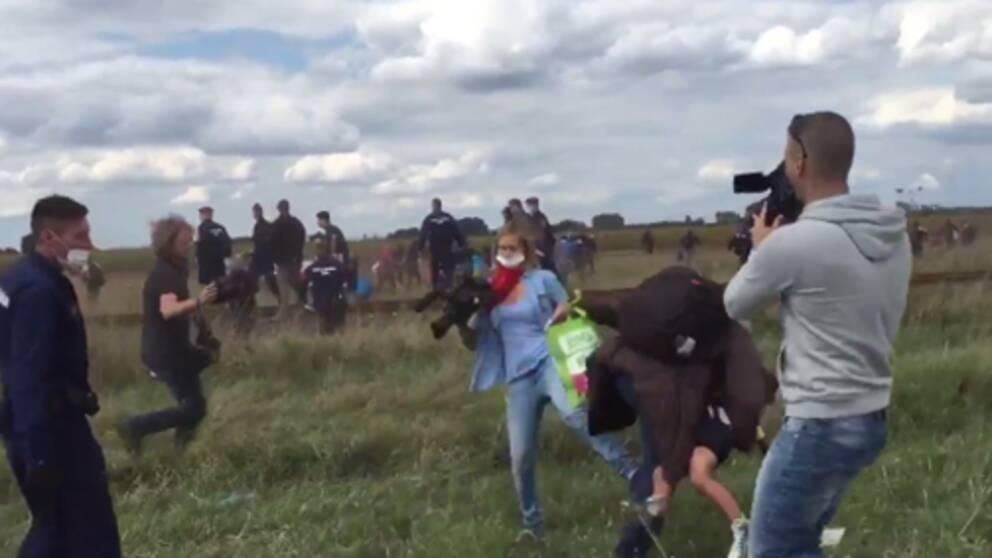 En ungersk journalist fäller krokben för en flyende man på ett fält utanför staden Röszke.