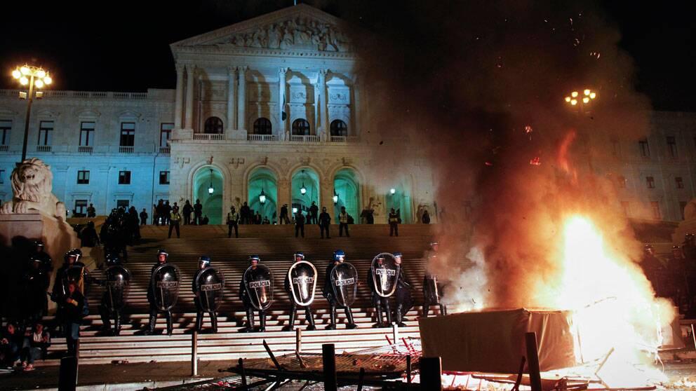 Poliser med kravallutrustning står brevid varandra framför parlamentsbyggnaden. I förgrunden brinner en eld som tänts av demonstranter. foto: scanpix