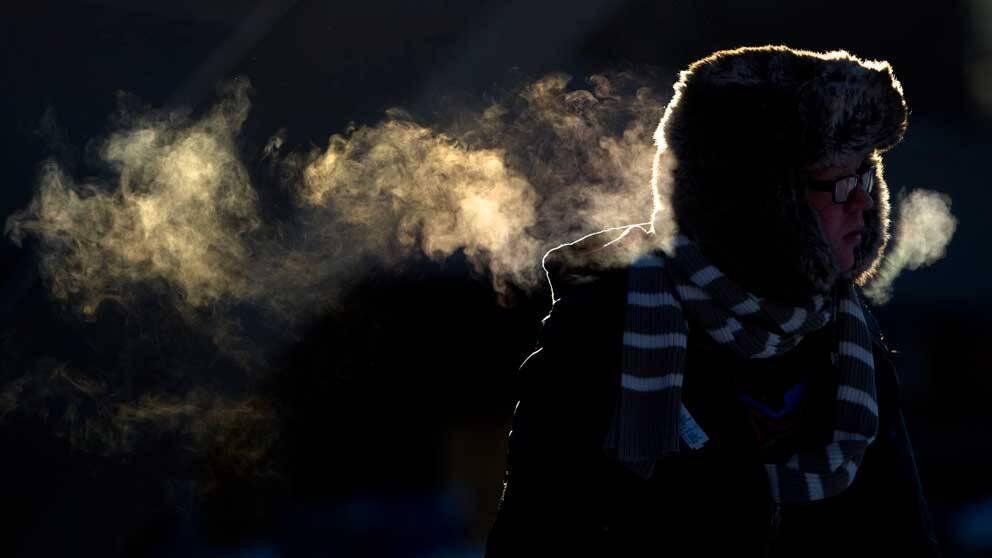 """Man i """"ryss-mössa"""" som andas ut """"rök"""" i kylan."""