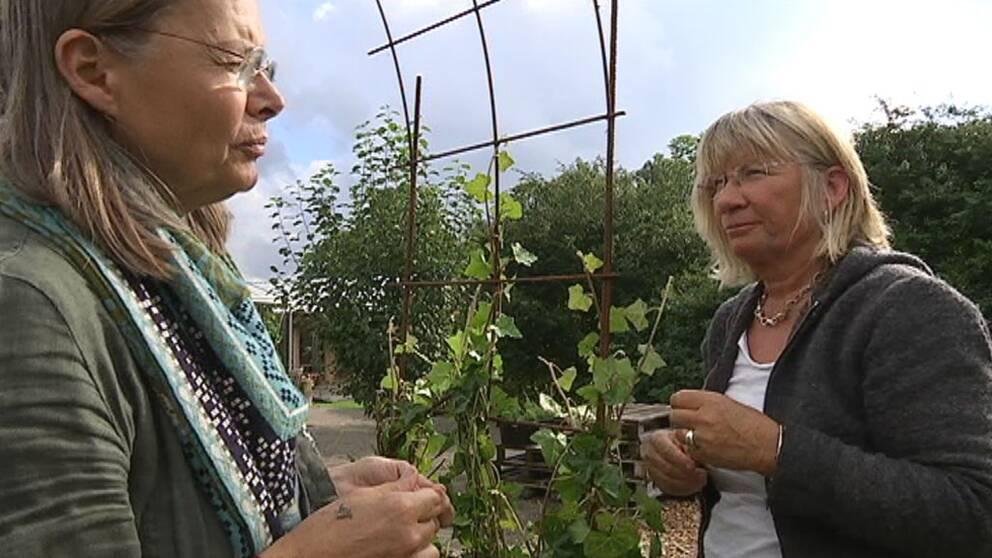 två kvinnor i närbild och en trädgård i bakgrunden.