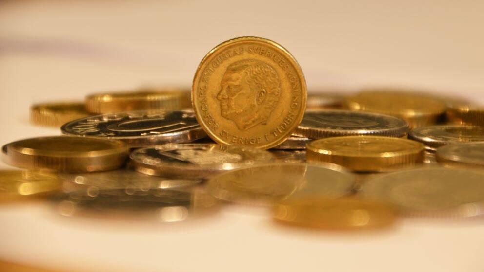 Tiokrona på hög av mynt.