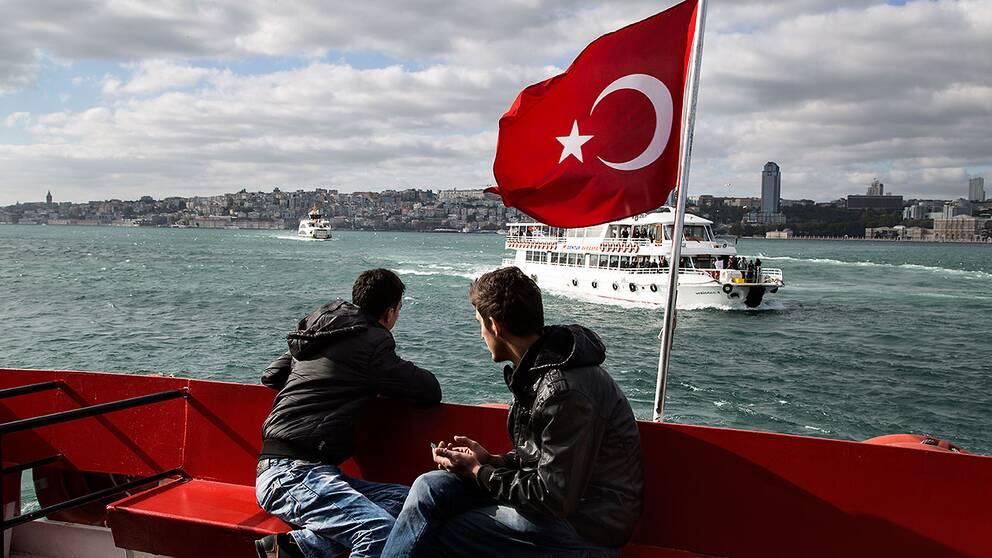 Turkiska män på en båt över Bosporen i Istanbul.