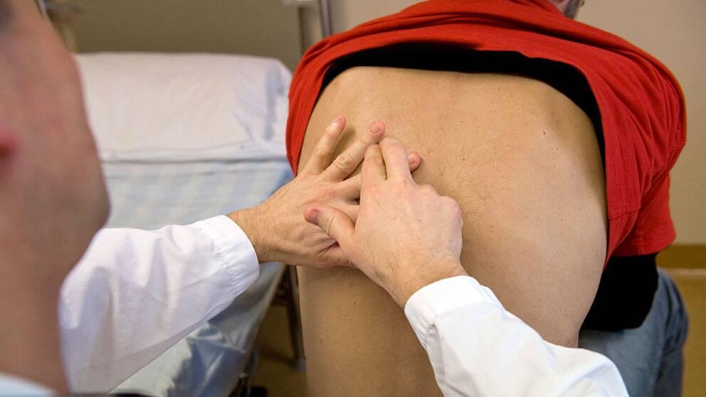 Läkare knackar patient på rygg