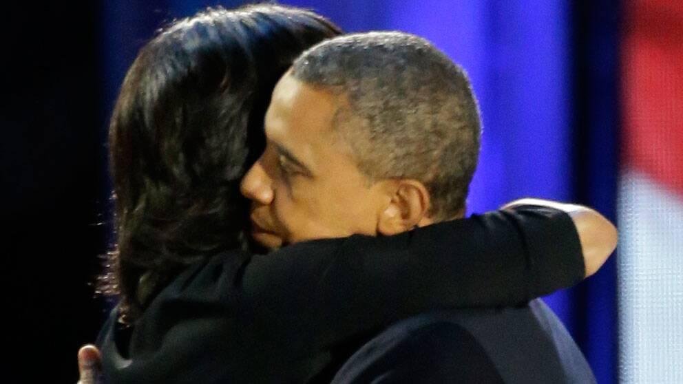President Obama omfamnar sin fru Michelle innan han lämnar scenen i Chicago.