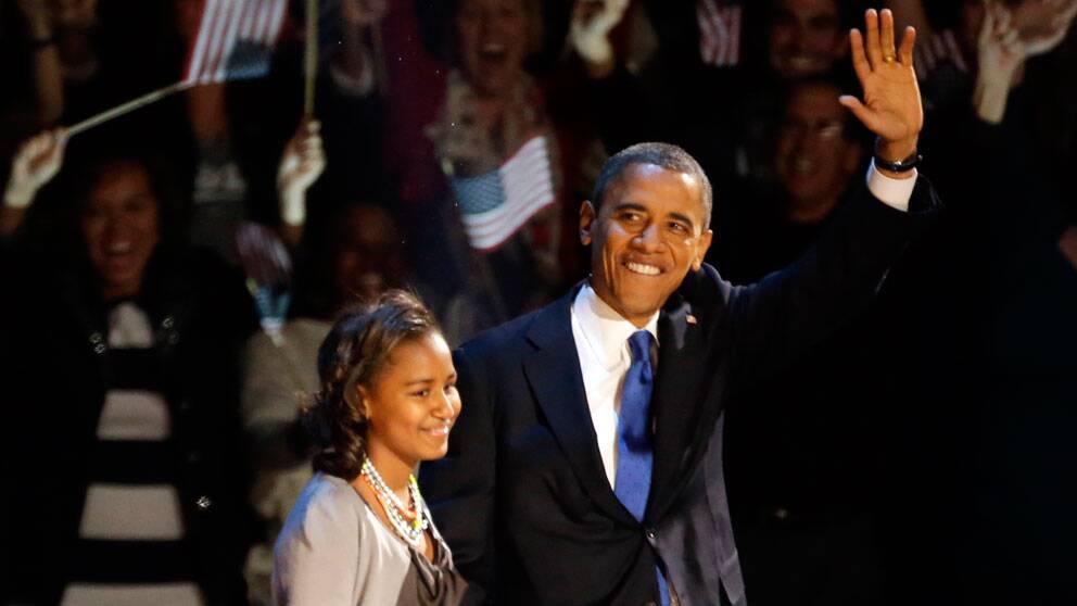 President Obama mottar publikens jubel på scen tillsammans med dottern Malia.