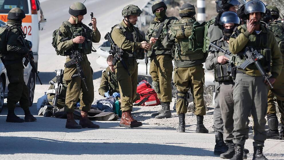 Israeliska soldater posterade runt kroppen av en palestinsk man som skjutits ihjäl efter att ha försökt hugga soldater på ockuperade Västbanken.