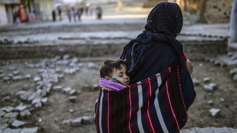En kvinna bär på sitt barn och vandrar förbi barrikaderna i staden Nusaybin i sydöstra Turkiet.