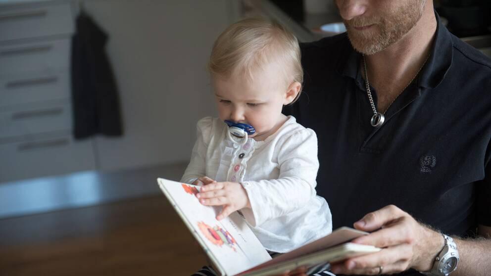 Pappa läser för sitt barn.