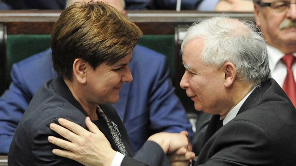 Premiärminister Beata Szydlo och Jaroslaw Kaczynski, ledare för partiet Lag och rättvisa, gratulerar varandra i polska parlamentet sedan den nya lagen om författningsdomstolen röstats genom.