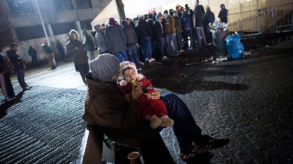 En syrisk man med sin dotter utanför ett registreringscenter för asylsökande i Berlin.