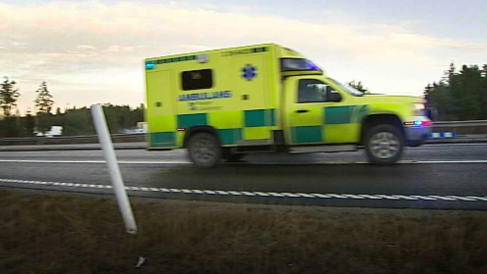 ambulans kör längs väg med skog bakom