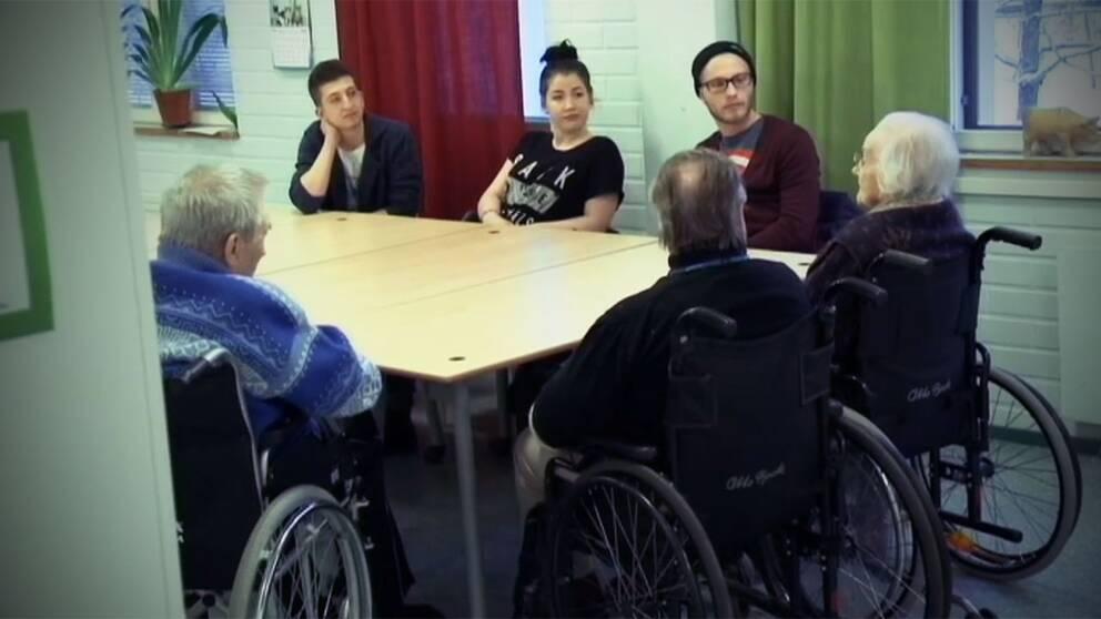 Experiment i Finland där unga flyttar till ett ädreboende. På bilden sitter två unga tillsammans med boende på äldreboendet.