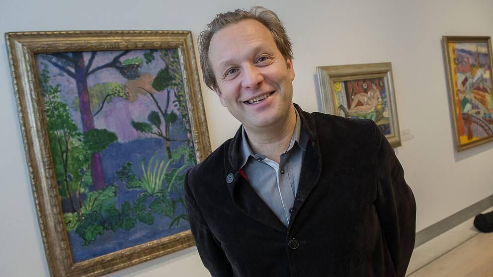 Daniel Birnbaum står framför några tavlor.