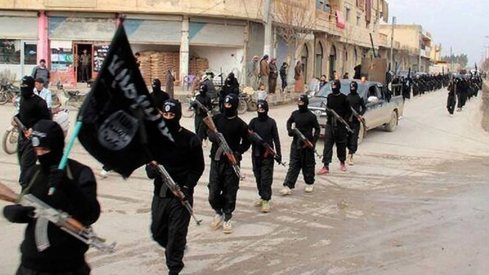 IS-krigare marscherar in i staden Raqqa i Syrien